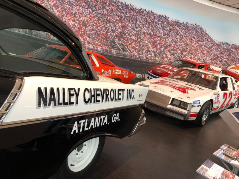 Old NASCAR cars on a slanted road with a photo of fans in the background