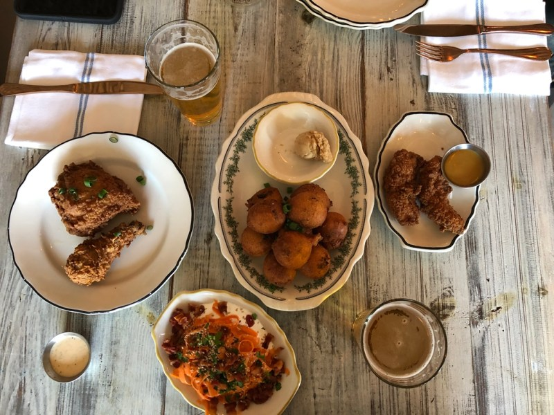 hushpuppies, fried chicken, sweet potato spirals, and beer on a table