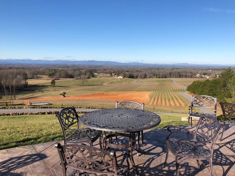 table and chairs with mountain landscape in the background at Piccione Vineyards