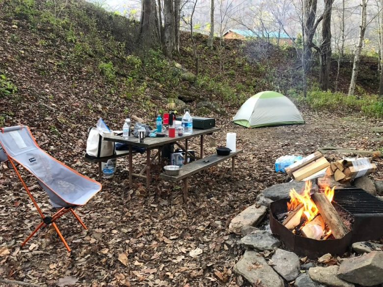 A Tent is set up with a picnic table, camping chair, and fire pit with a fire going. All of the necessary tent camping gear.