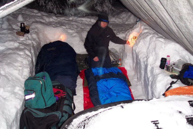 Sleeping bags and sleeping pads laid out in the snow. Camping in winter.