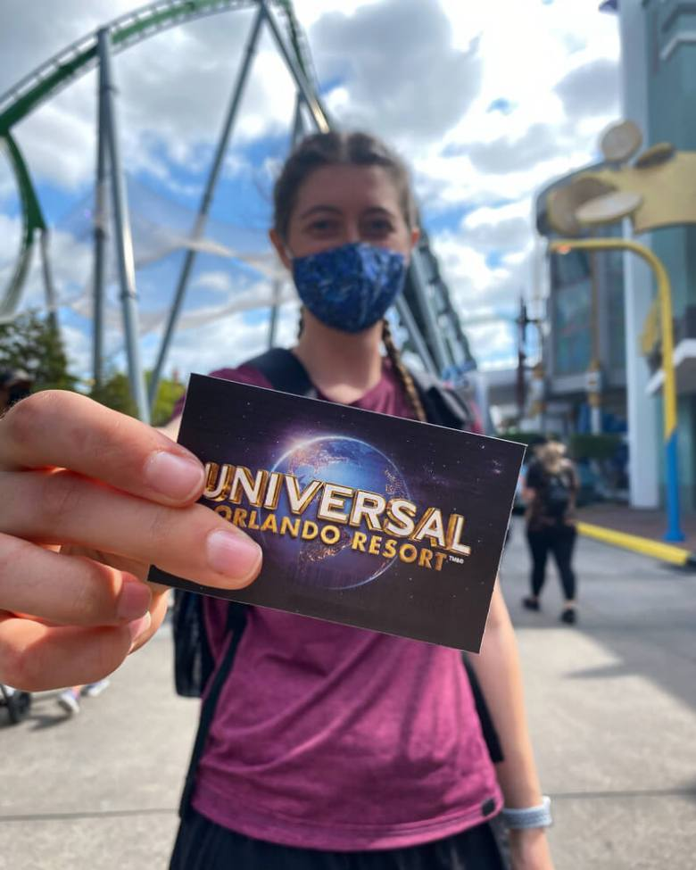 Universal Orlando Resort express pass in front of a girl's face. Buying the express pass is one of my top tips for visiting Universal Studios.