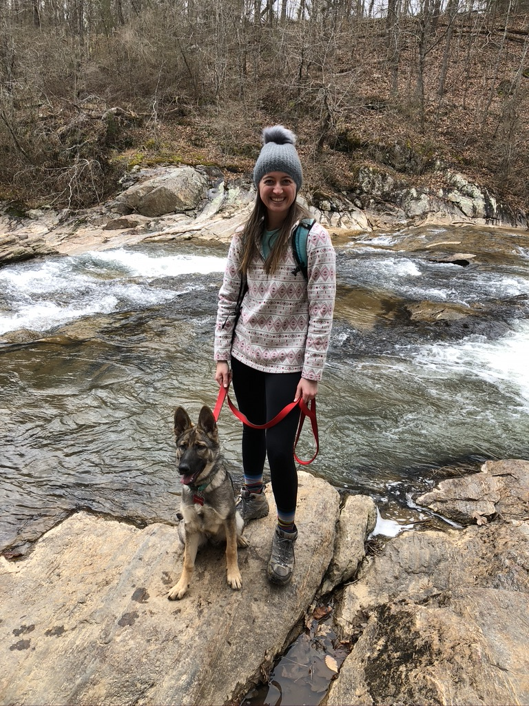 Girl standing next to dog on a leash in front of a creek. Hiking while tent camping with dogs.