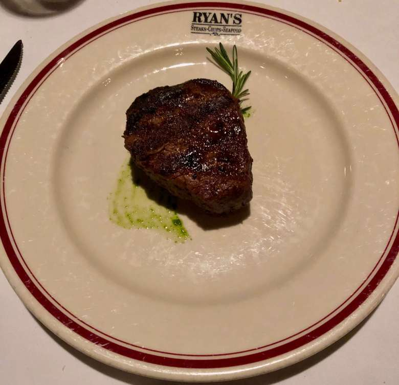 Steak on rosemary sprig and a white plate at one of the best downtown Winston-Salem restaurants.