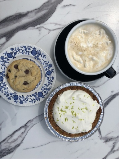 A cookie, coffee, and key lime pie against a marble background.