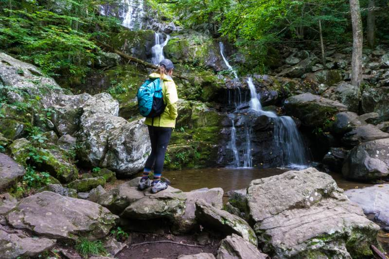 woman in front of waterfall - hikes in Shenandoah National Park