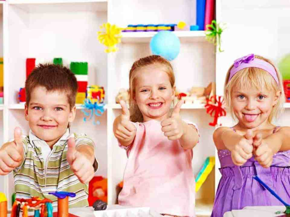 three children in the classroom giving thumbs up with big smiles