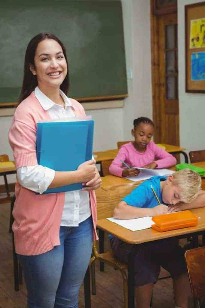 smiling teacher holds binder while children work at desks in the classroom