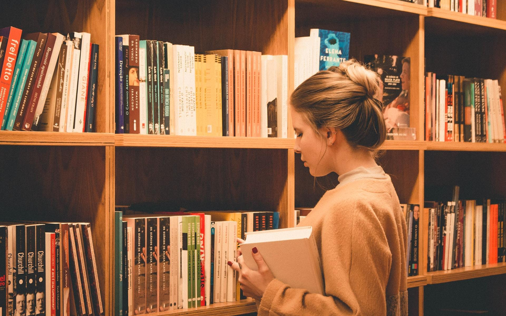 Person standing inform of bookshelf looking at books