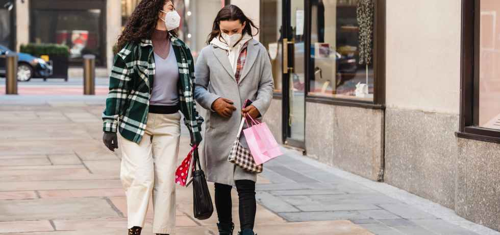 stylish friends in protective masks walking on street
