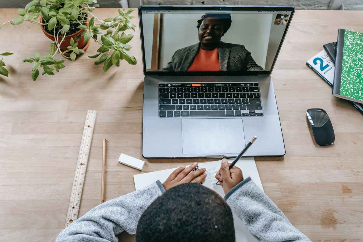 black teacher on laptop screen during lesson with crop schoolboy