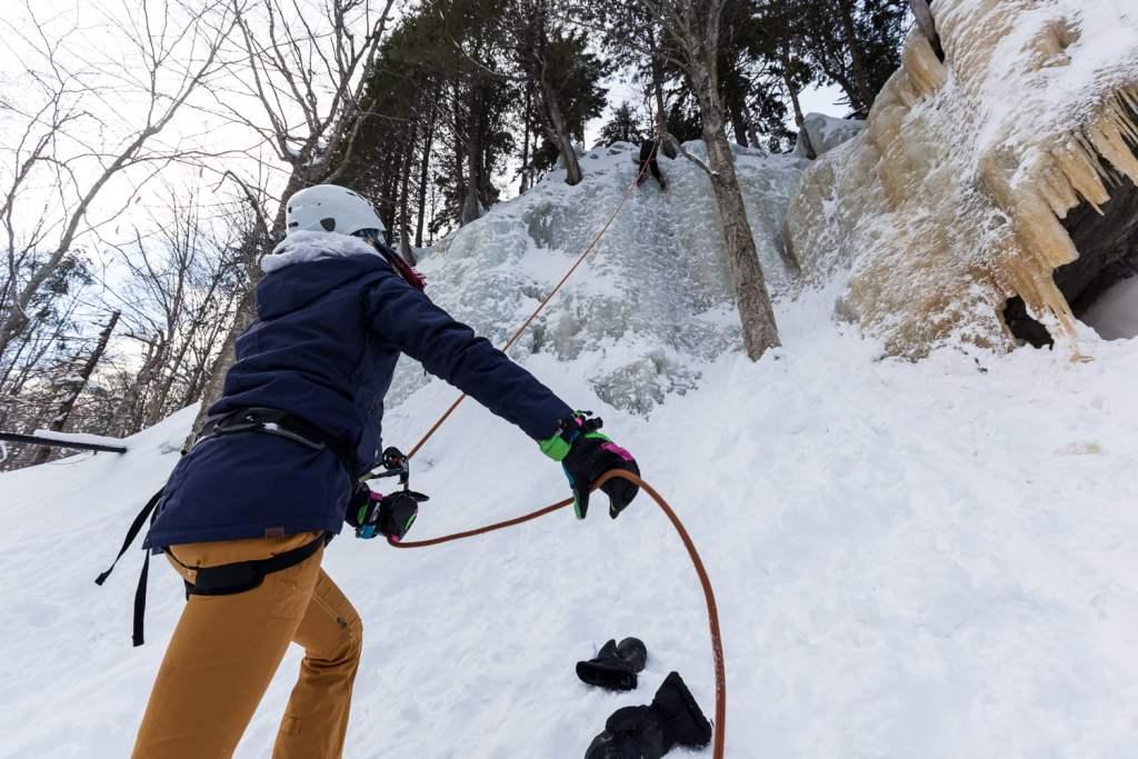 personne assurant un grimpeur sur une aproi de glace