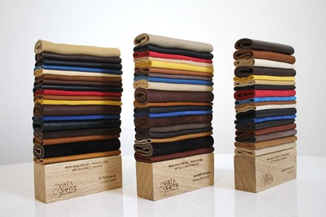 Photo de 3 trophées en cuir recyclé et bois, trophée rectangulaire verticale, gravure sur bois, superposition de chutes de cuir plié, mixte couleurs, concours récompenses RSE