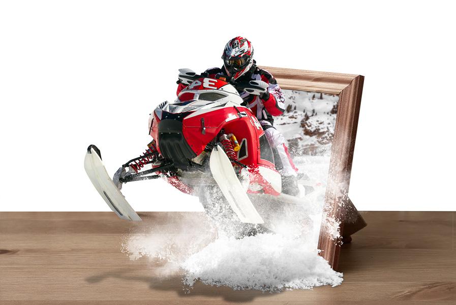Beeldmanipulatie van een sneeuwscooter die uit een fotolijst springt