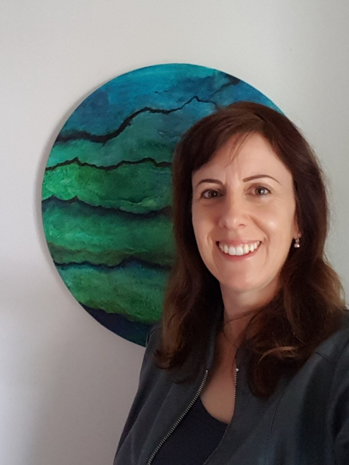 Image of artist with painting in background