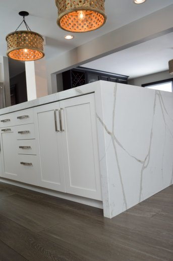 White cabinetry and quartz island