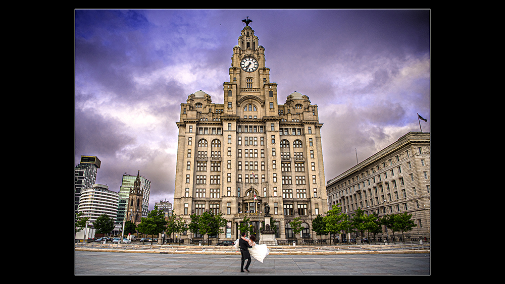 Groom carries his bride in front of Liver buildings in Liverpool