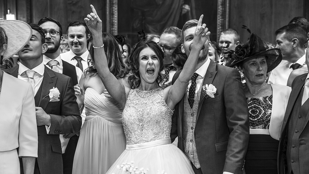 bride living the moment as photographer takes group shot