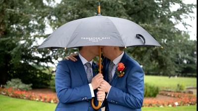 Husbands' first kiss under umbrella