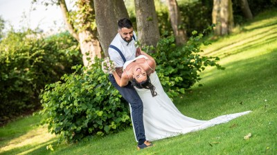 Bride tilts back laughing with groom