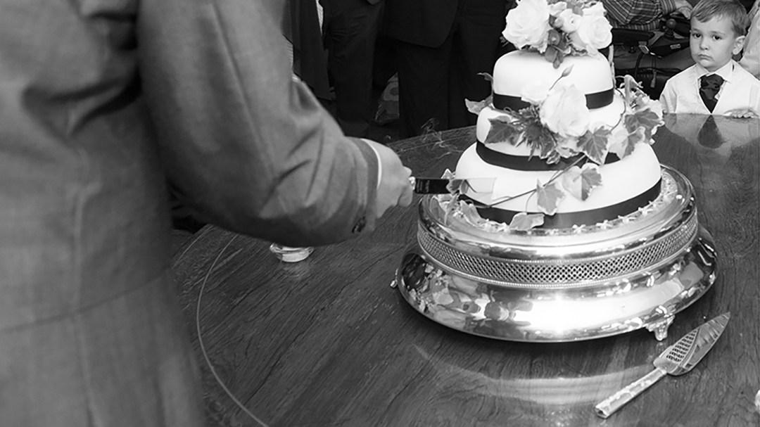 Wedding ckae cutting hungry child looks on