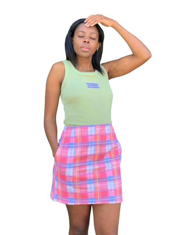 Feminine model standing with her hand in her hair and another in the pocket of the Candor Cher skirt, paired with a mint Candor tank top against a white backdrop. The skirt is pink with a pink and blue tartan print mini with an elasticated waist. It is named after Cher from the movie Clueless for its iconic print and style.