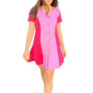 Feminine model wearing the short-sleeved Candor Sakura dress with sunglasses and brown buckled boots. The dress is corduroy and baby pink with wide, hot-pink panels on the side and on the sleeves. It is mini-length with a slight flare at the hips. The dress is V-necked with six metal stud buttons all the way down the middle.
