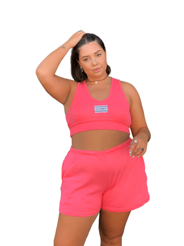Feminine model, wearing the Oleander set running a hand through her hair with the other over her pocket, smiling into camera against a white backdrop. The Oleander set is a light, but bright pink with pockets on the shorts and a cropped bralette with Candor label on the centre front.