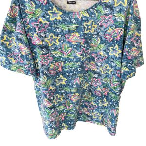 Cotton-blend blue t-shirt with printed vintage patterns all over, of yellow stars, pink fish and various brightly-coloured shapes. Against a plain white background.