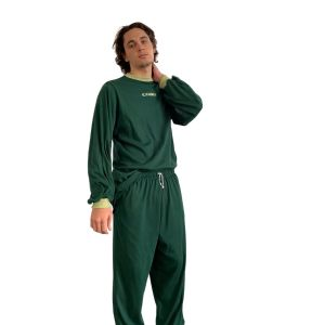 Masculine model standing against a plain white background, wearing dark green long-sleeved top and matching pants in the same fabric. Candor logo is embroidered centre front of the shirt, and sleeves and neck have vintage-style light green rib cuffs.