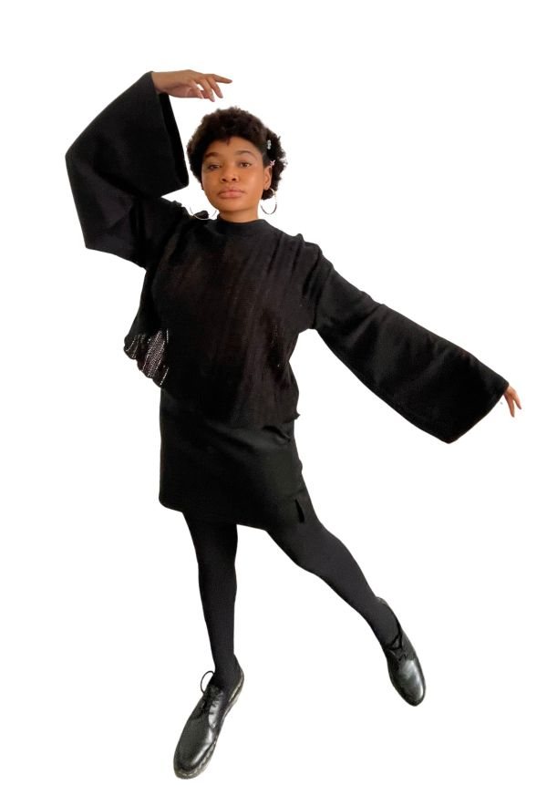 Feminine model standing facing forward, wearing black knit sweater vest top with flared long-sleeves, and black faux leather-style mini skirt. The model is wearing stockings and low-top Doctor Martens shoes and pulling a whimsical pose.