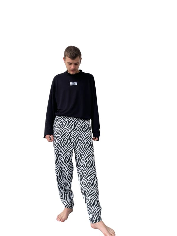 Masculine caucasian model standing against a plain white background, barefoot, looking down at his feet. The model is wearing a plain black long-sleeve shirt with a high collar and a Candor label at a 7cm drop centre front. The model is also wearing the Candor Marty pants, which are made from a stretch fabric in a zebra print. The pants have an elasticated waistband and are subtly tapered down to a straight hem. The pants do not have pockets.