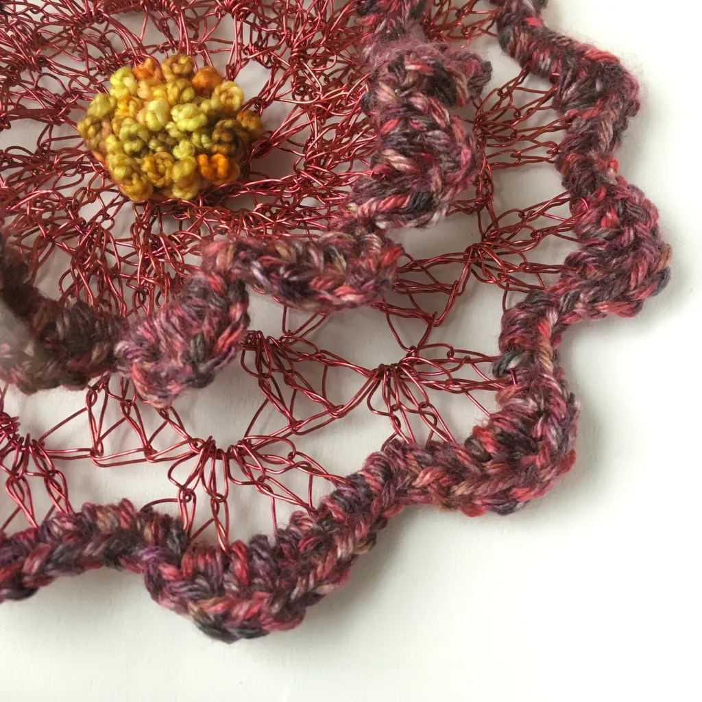 Detail photograph of wire and fiber hand crafted flower wall art