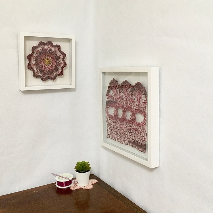 Two framed wire crocheted artworks in a lovely little nook, Raspberry Lace with Flower