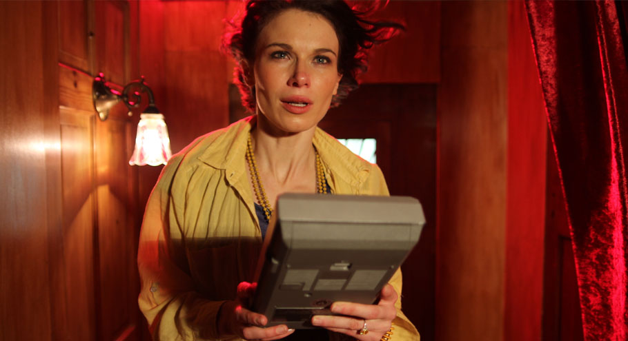 Georgina Sherrington holding a vintage tape recorder in the short film Stop Eject by Neil Oseman