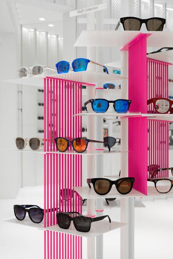 Soporte para exposición de gafas en interior de tienda blanco y fucsia