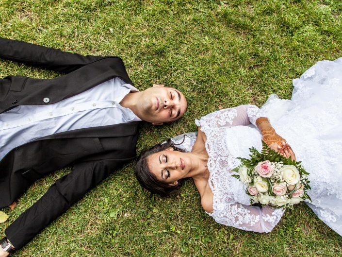 couple de mariés dormant sur herbe avec bouquet de mariage