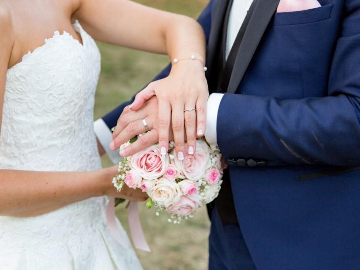image avec un couple de mariés posant la main sur un bouquet