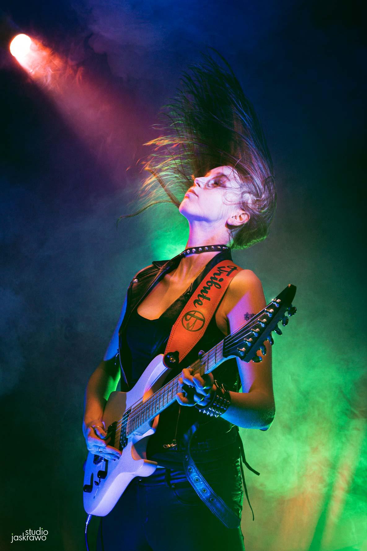 dziewczyna z gitarą na scenie muzycznej podczas koncertu rockowego