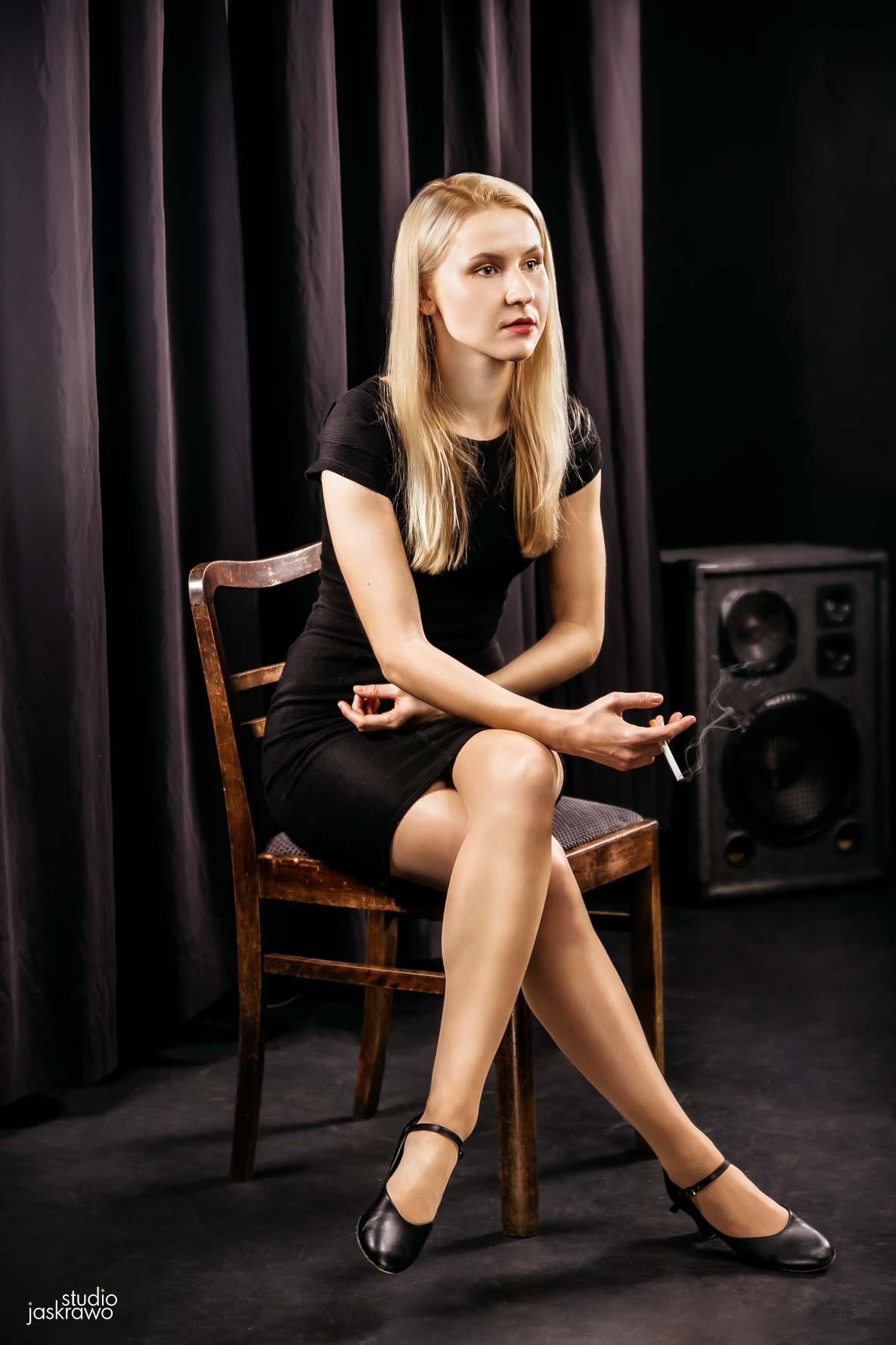 kobieta siedzi na krześle i trzyma w dłoni papierosa