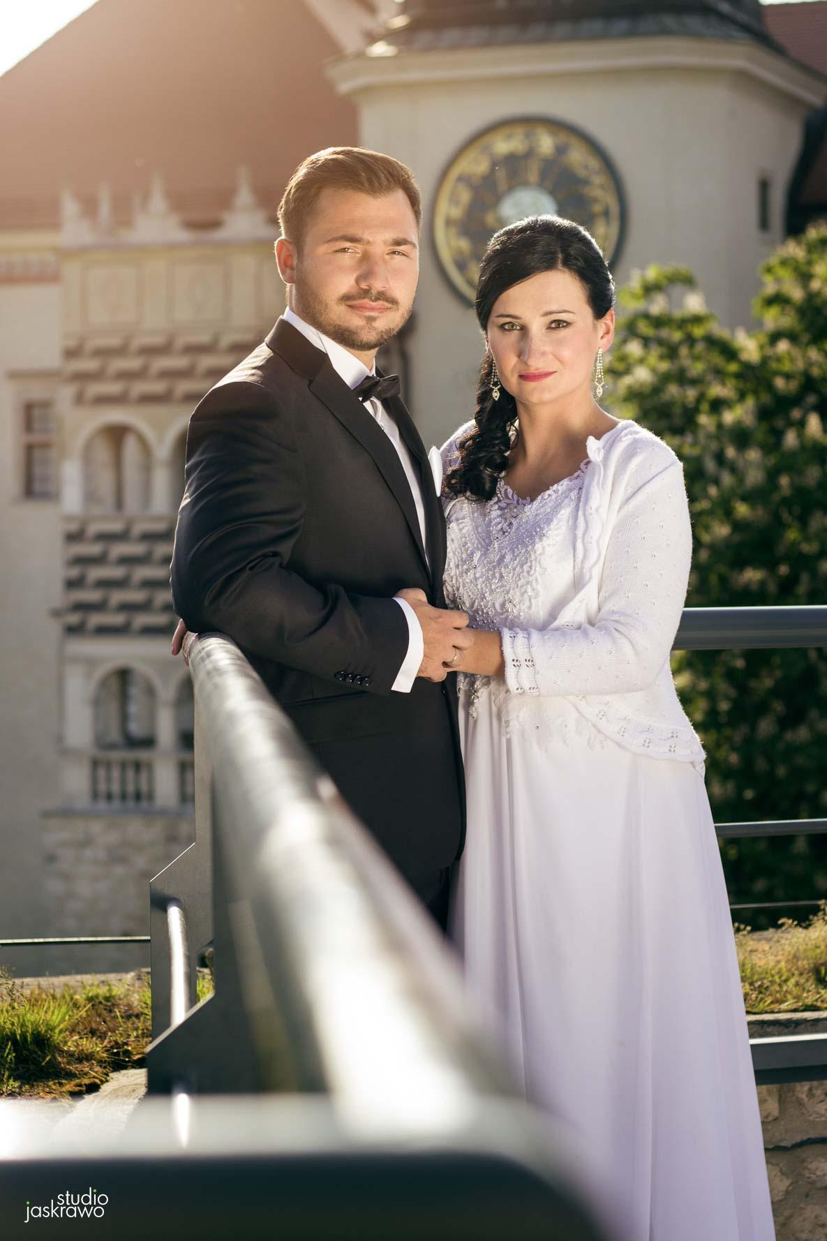 nowożeńcy na tle pałacu, mężczyzna w garniturze po lewo, kobieta w sukni po prawo