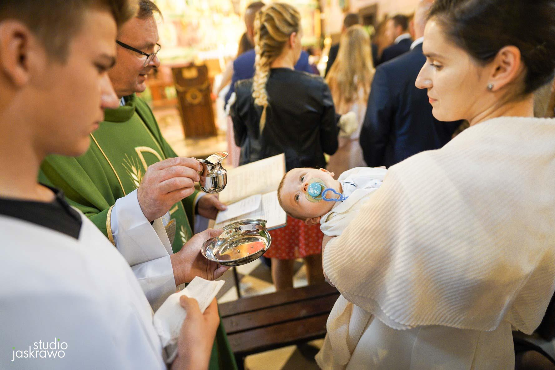 matka podaje dziecko do chrztu, ksiądz trzyma wodę święconą