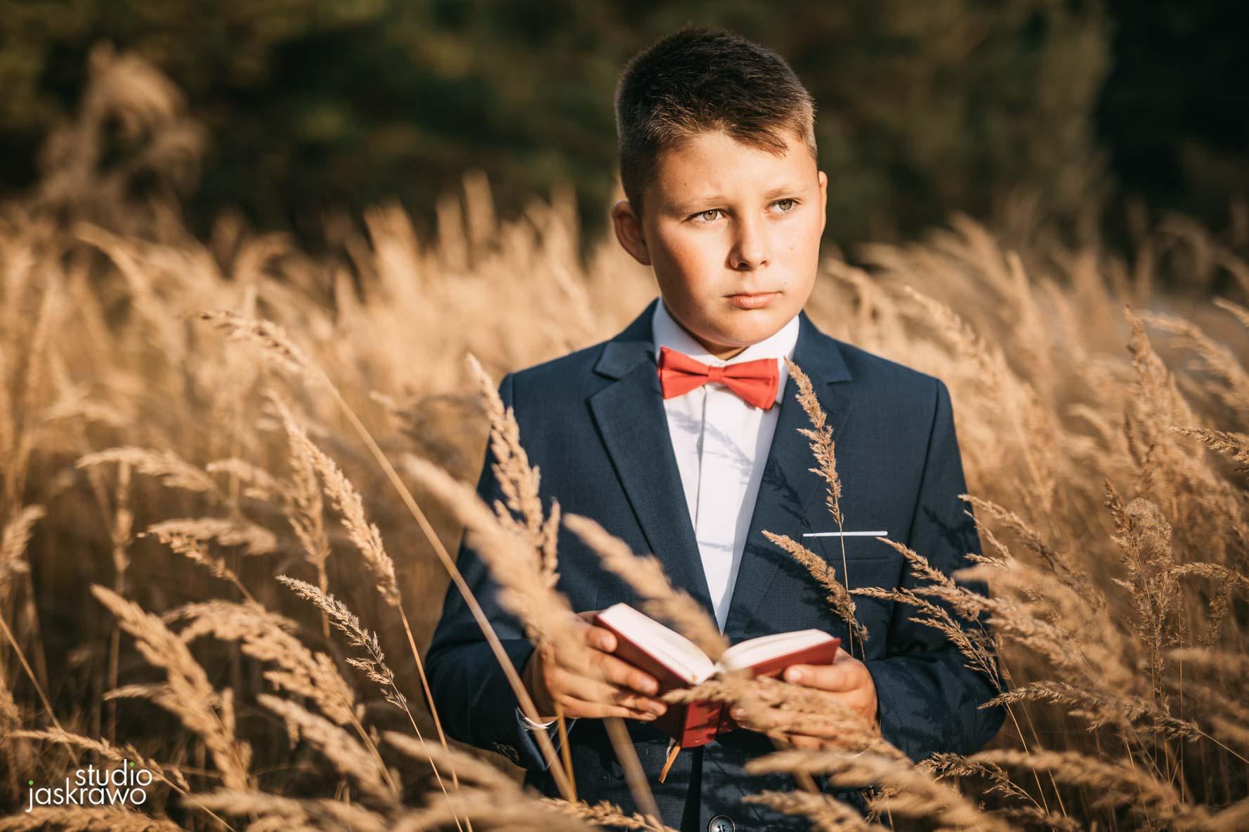 Młody chłopiec w garniturze trzyma w rękach książeczkę z pierwszej komunii świętej