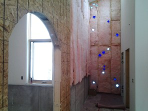 """Glass bottles in entry wall with view through """"brick"""" arch"""