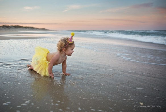 1st birthday photo shoot with party hat and yellow tutu on beach at Nags head NC