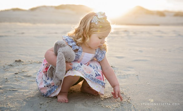 Photograph of young girl drawing in the sand and her bunny in Outer Banks NC