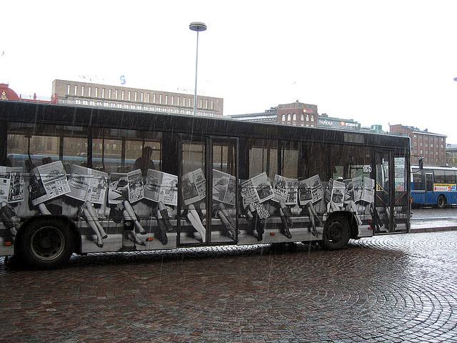 Newspaper people on bus / Helsinki 2006