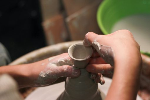Close-up from above of two hands throwing a vase on a potter's wheel.