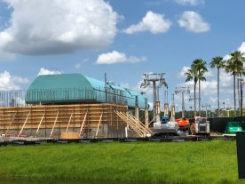 Construction crews have made good progress in completing the Park station's roof. Both ends of the gondola arrival and departure structure are now enclosed. A new section of the skyliner's cabling structure has been positioned adjacent to the station entrance along with other adjacent column framing. This continued progress advances this innovative guest aerial transportation system forward toward future final completion. Disney's Hollywood Studios. Photo by John Capos