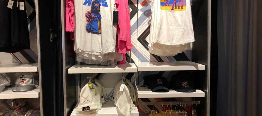 Guests exiting the Rock'n' Roller Coaster Starring Aerosmith attraction will find new Star Wars themed women's clothing waiting in the Rock Around The Shop. Shoppers can select from a white stocking cap featuring two clashing lightsabers or black caps with a choice of either Darth Vader or Millennium Falcon images. Additional merchandise includes a women's retro pink and grey tee shirt favoring the Dark Side with a Darth Vader image. Those on the Light Side can select a jet black tee shirt with stunning Star Wars lettering. Tank top fashions include either a white top with two advancing AT-AT vehicles or a yellow tank style featuring the lovable Wicket the Ewok. Disney's Hollywood Studios. Photo by John Capos